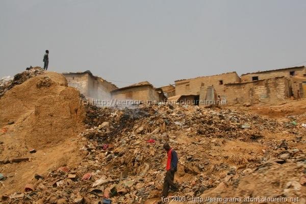 Pessoas a caminhar sobre montes de lixo a arder