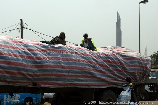 Dois funcionários viajam deitados sobre a carga no semi-atrelado